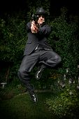 Man In Suit Jumping With Gun