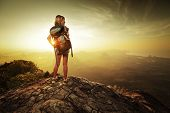 Lady hiker with backpack standing on top of a mountain and enjoying sunrise