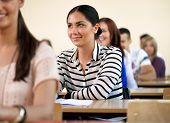 Fröhlich weibliche Studentin, die in einem Klassenzimmer voller Studenten sitzen