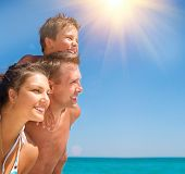 Happy Young Family with Little Child Having Fun at the Beach. Joyful Family. Travel and Vacation Con