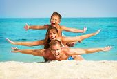 stock photo of lie  - Happy Young Family with Little Kid Having Fun at the Beach - JPG