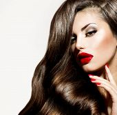 Sexy Beauty Girl with Red Lips and Nails. Make up. Luxury Woman with Long Curly Hair. Fashion Brunet