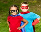 stock photo of arms race  - Pretty mixed race girl and Caucasian boy pretending to be superhero - JPG