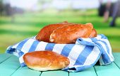 Fresh baked pasties, on wooden table, on bright background