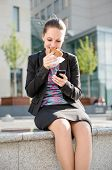 Business woman eating and working with phone