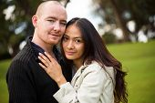 Close up portrait of a young attractive romantic couple, caucasian man, asian woman, in a beautiful