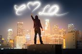 Graffiti artist on rooftop in downtown Los Angeles painting love LA message over night sky with light.
