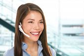 Headset customer service woman secretary at call center talking friendly smiling happy in office. Beautiful young mixed race Caucasian / Asian Chinese business woman working at hotline.