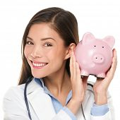 Healthcare concept - doctor holding piggy bank. Health care concept. Medical insurance or similar. Happy doctor woman shaking piggy bank looking smiling. Nurse or physician money concept isolated.