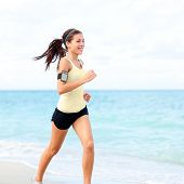 stock photo of arms race  - Running woman jogging on beach listening to music in earphones from smart phone mp3 player smartphone armband - JPG