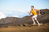 Running sport runner man sprinting in trail run. Fit male fitness sports athlete training sprint in amazing outdoor trail on volcano. Strength and success concept in compression shorts. Full body.