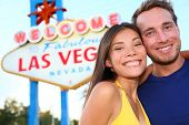 Las Vegas tourist couple at Las Vegas sign. Happy tourist couple taking self-portrait in front of Welcome to Fabulous Las Vegas sign. Beautiful young multi-ethnic people, Asian Woman, Caucasian man.
