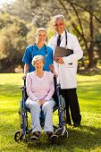 caring healthcare workers outdoors with disabled senior patient