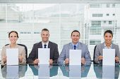 Smiling interview panel in bright office holding white paper sheets
