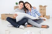 stock photo of legs apart  - Portrait of man and woman holding house plans in their new house - JPG