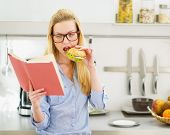 Teenager Girl Having Burger In Kitchen While Studying