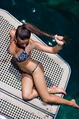 Young woman in bikini on her private yacht deck