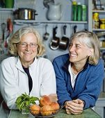 Smiling senior women leaning at kitchen counter