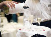 Champagne se vierte en una flauta de champagne por camareros