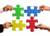 Teamwork strategy or partnership concept with business team holding jigsaw pieces together