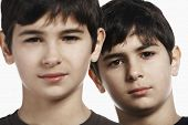 Closeup portrait of confident preadolescent siblings isolated over white background