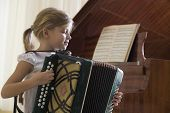 Side view of a young girl playing the accordion