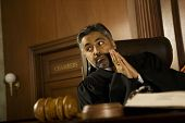 Thoughtful male judge with hands clasped looking away in court room