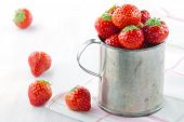 Red Strawberries In An Old Metal Measurement Cup