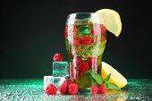 Iced tea with raspberries and mint on dark background with green light