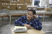 Portrait of a bored Asian woman sitting with clipboard in distribution warehouse