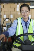 Portrait of a cheerful Asian woman working in distribution warehouse