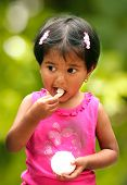 Beautiful Young Indian Girl Child Enjoying Ice Cream In A Park.