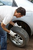 The man changes the punctured wheel of the car.
