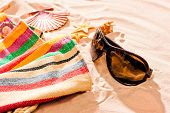 Striped Beach Towel And Sunglasses On A Sandy Beach
