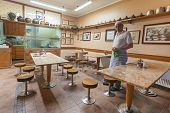 SARAJEVO, BOSNIA AND HERZEGOVINA - AUGUST 13, 2012: Owner cleans restaurant tables after long day at