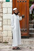 SARAJEVO, BOSNIA AND HERZEGOVINA - AUGUST 13, 2012: Religious Muslim man with cell phone stands on street close to main mosque in old town Sarajevo.