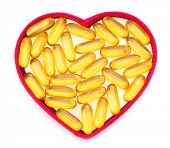 Fish oil pills in red heart shaped box isolated on white background