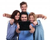 young group of people showing you the blank screen of a tablet pad computer and point fingers to the