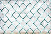 image of chain link fence  - Chain link fence on white brick blur background - JPG