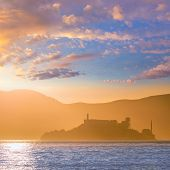 Alcatraz island penitentiary at sunset and backlit in San Francisco, California, USA.