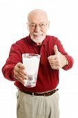 Handsome senior man holding a glass of ice water and giving a thumbs up.  Isolated on white.