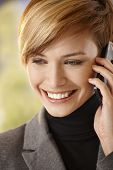 Closeup portrait of happy young woman talking on mobile phone