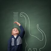 Young boy measuring his growth in height against a blackboard with chalk dinosaur scale