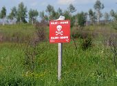 stock photo of land-mass  - Sign warning on land mines field at war zone - JPG