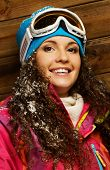Smiling woman in ski jacket and ski mask against wooden house wall