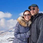 Closeup portrait of happy young family having fun in wintertime mountains, wearing fashionable sunglasses, love and togetherness conception