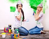 Happy woman paint wall at home.