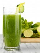 Glass of green vegetable juice and vegetables on wooden table on white background