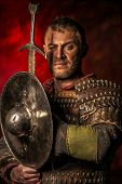 stock photo of sword  - Portrait of a courageous ancient warrior in armor with sword and shield - JPG