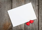 Valentine's day blank gift card and red candy hearts on wooden background